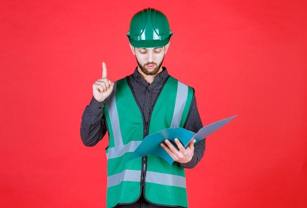 Engenheiro de uniforme verde e capacete segurando uma pasta azul, lendo e fazendo correções.