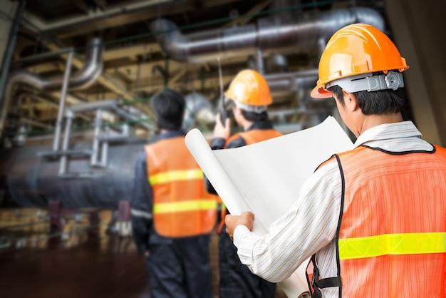 Engenheiro do governo em uniforme de segurança com papel de registro no edifício interior da usina