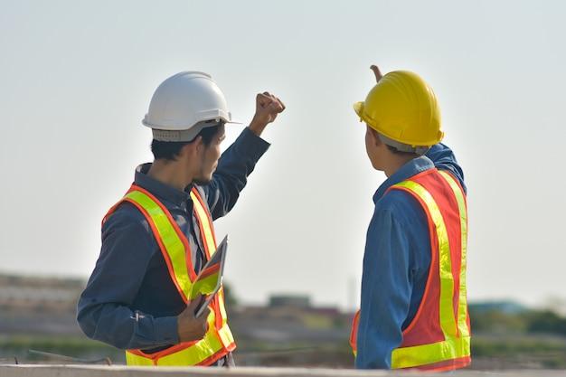 Engenheiro, duas pessoas colocar a mão no sucesso na luz do sol céu, construção de supervisor capataz