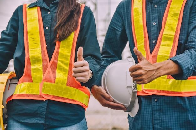 Engenheiro, duas pessoas segurando capacete usar roupa de segurança