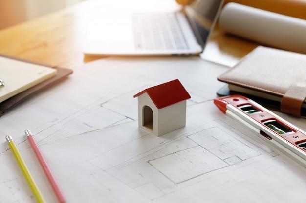 Engenheiro e arquiteto conceito, close-up modelo de casa na mesa do designer de interiores com planta