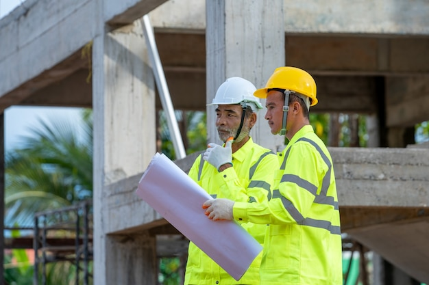 Engenheiro e arquiteto discutindo reunião com a planta e idéias sobre a construção de estrutura no canteiro de obras.