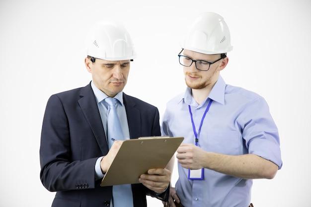 Engenheiro e arquiteto em capacetes discutem o projeto enquanto fazem anotações na área de transferência