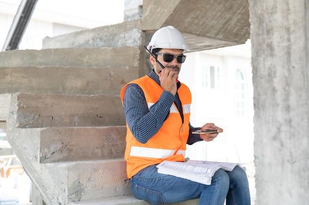 Engenheiro e arquiteto trabalhando no canteiro de obras com impressão azul.