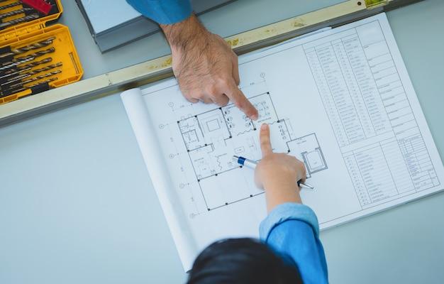 Engenheiro, e, arquitetos, discutir, e, apontar, para, disposição, predios, em, desenhos técnicos, ligado, tabela, em, fábrica