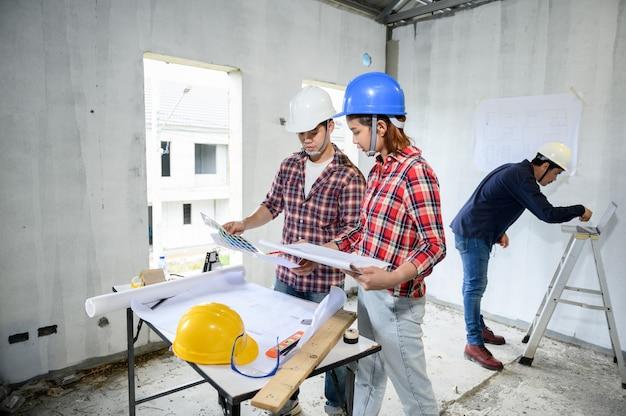 Engenheiro e arquitetos trabalhando e discutindo no canteiro de obras. inspeção do proprietário no projeto da vila e na construção da propriedade.