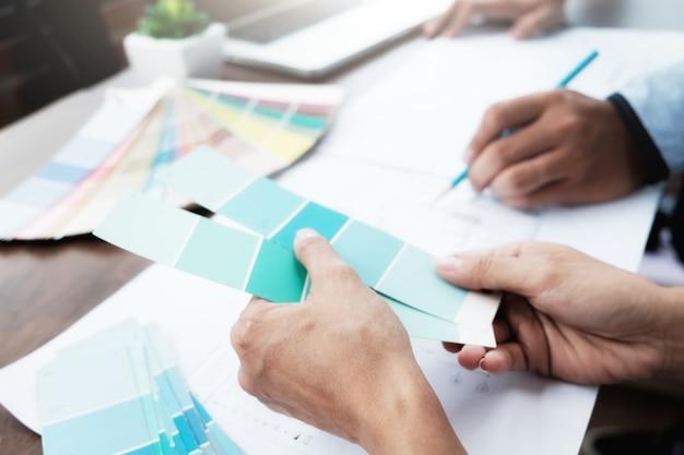 Engenheiro e arquitetura selecionam cor para projeto de casa.