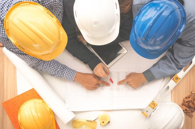 Engenheiro e capataz usando capacete de segurança estão reunidos no site ao ar livre e apontando para o papel de desenho