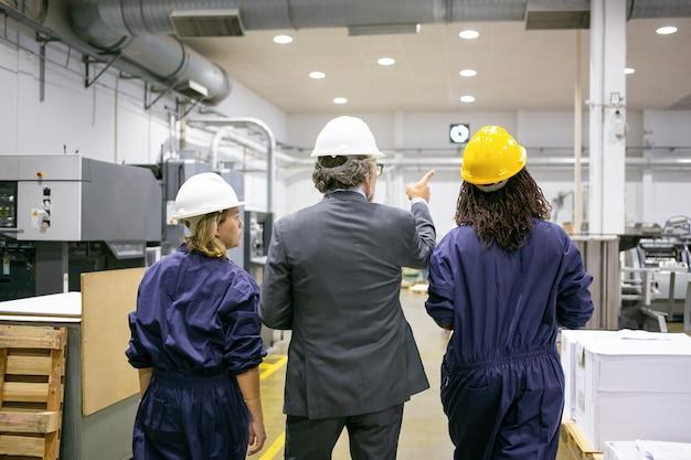 Engenheiro e funcionárias de fábrica em capacetes, andando no chão da fábrica e conversando, homem apontando para o equipamento e instruindo mulheres