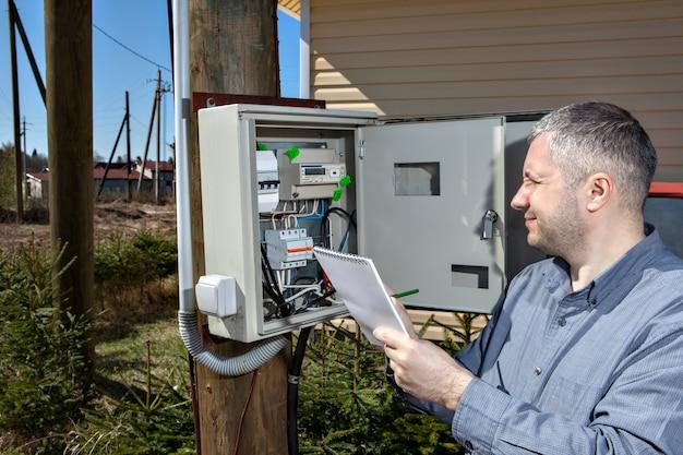 Engenheiro eletricista do país inspecionando o equipamento do contador elétrico na caixa de distribuição.