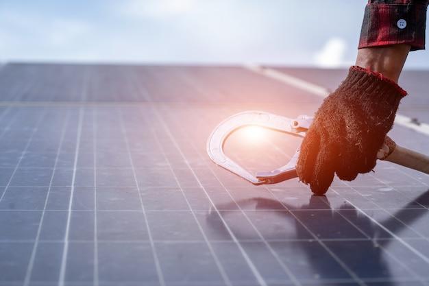 Engenheiro eletricista ou técnico de manutenção do sistema elétrico trabalhando na verificação e manutenção de equipamentos na usina solar, conceito de energia alternativa limpa e verde.