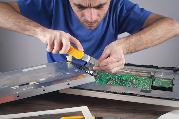 Engenheiro eletricista que repara o monitor do computador.