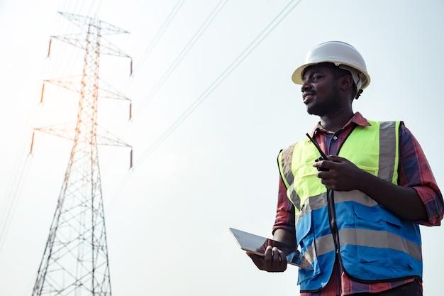 Engenheiro elétrico americano da áfrica com poste de eletricidade de alta tensão e usando walkie talkie e tablet para controlar o assistente