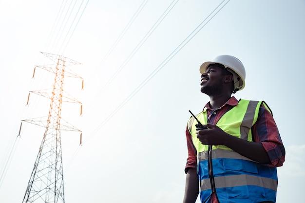 Engenheiro elétrico americano da áfrica com um poste de eletricidade de alta tensão e usando um walkie-talkie para controlar o assistente