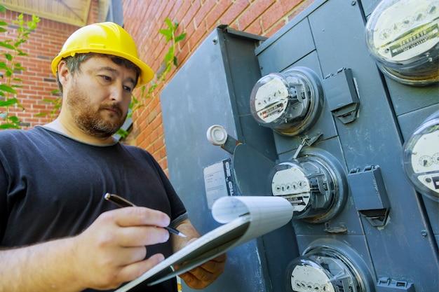 Engenheiro elétrico durante a verificação, técnico de capacete amarelo examinando a leitura do medidor na área de transferência