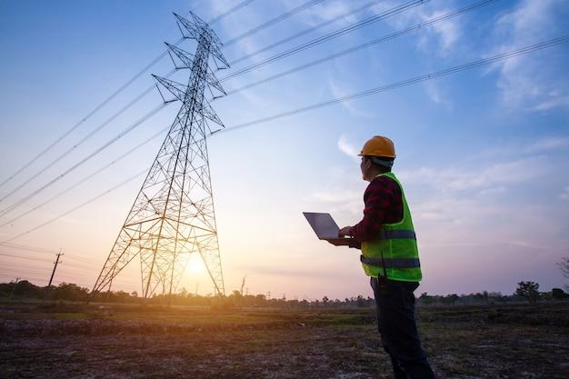 Engenheiro elétrico em pé e observando na estação de energia elétrica