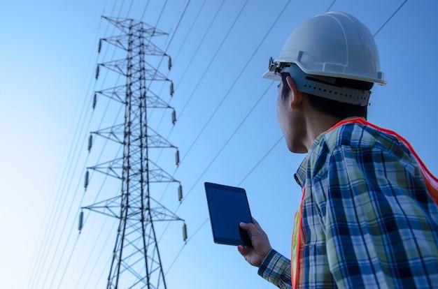 Engenheiro elétrico segurando e usando um tablet digital