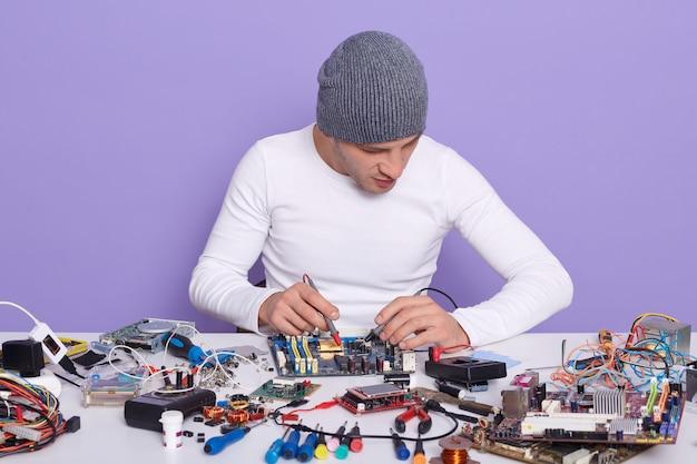 Engenheiro eletrônico medindo a tensão da placa de circuito eletrônico com a ajuda do multimete