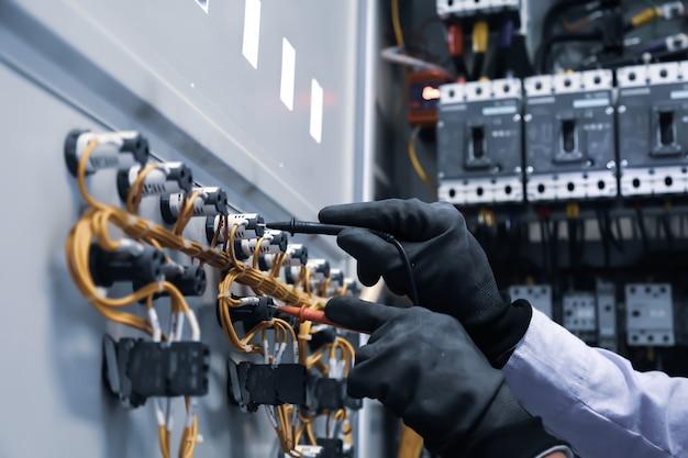 Engenheiro eletrotécnico que usa o equipamento de medição para verificar a tensão atual elétrica no disjuntor.