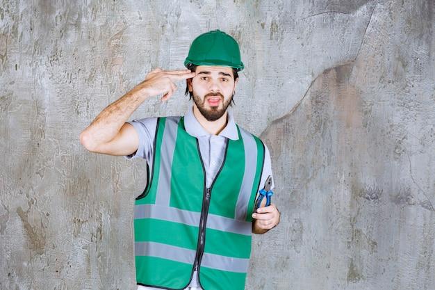 Engenheiro em engrenagem amarela e capacete segurando um alicate.