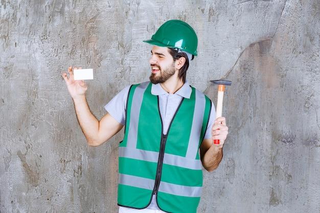 Engenheiro em engrenagem amarela e capacete segurando um machado com cabo de madeira e apresentando seu cartão de visita.