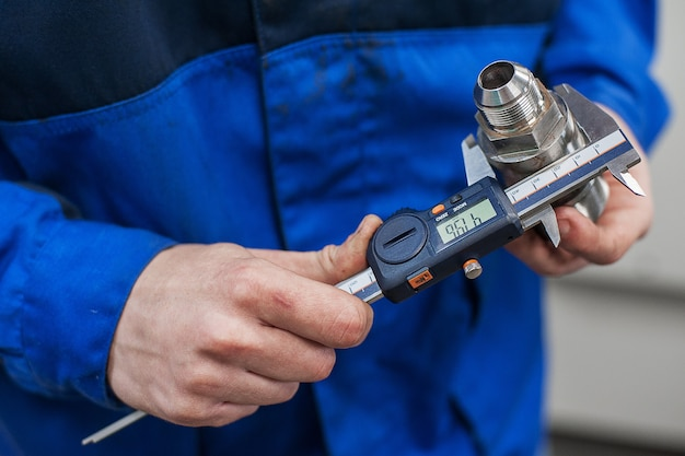 Engenheiro em fábrica com aprendiz verifica qualidade do componente
