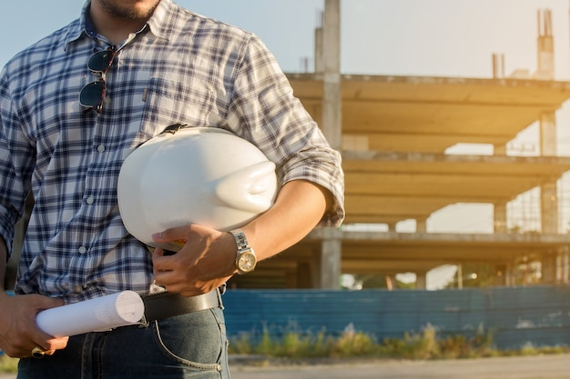 Engenheiro em profissional segurando um capacete de pé no canteiro de obras da frente.