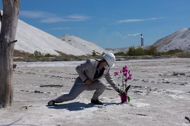 Engenheiro em um capacete branco no contexto da zona industrial protege uma flor de orquídea. conceito ecológico de proteção ambiental.