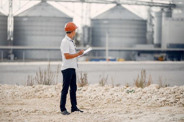 Engenheiro em um capacete de pé junto à fábrica