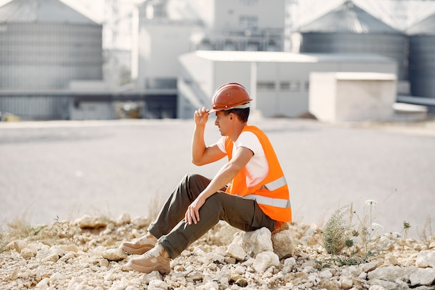 Engenheiro em um capacete sentado perto da fábrica