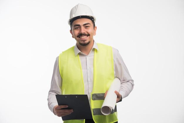 Engenheiro em uniforme segurando plano de projeto e lista de tarefas.