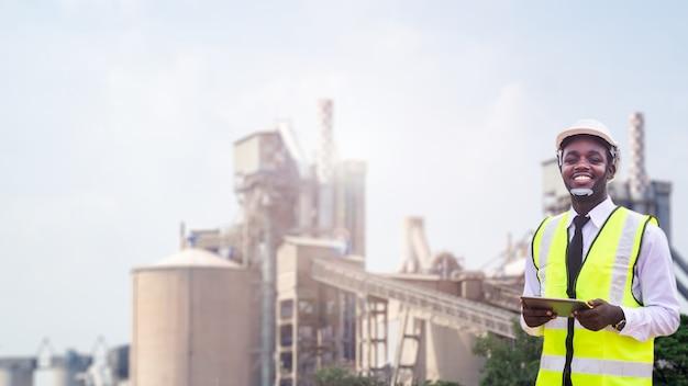 Engenheiro empreiteiro africano com capacete segurando tablet com fábrica em segundo plano