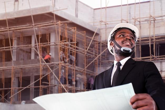 Engenheiro empreiteiro africano com capacete segurando um papel de impressão azul com o prédio ao fundo