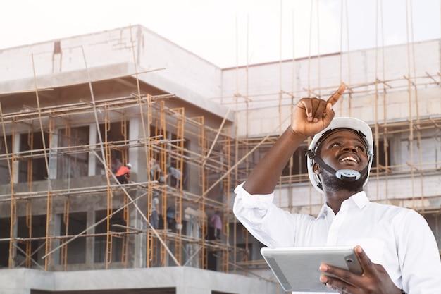 Engenheiro empreiteiro africano com capacete segurando um tablet com o prédio ao fundo