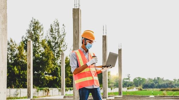 Engenheiro empreiteiro homem usa laptop trabalho projeto da indústria no local de estruturas de construção de edifícios