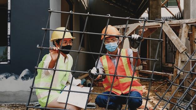 Engenheiro empreiteiro reunião da equipe do trabalho de construção do projeto verificar o projeto da planta da casa no canteiro de obras