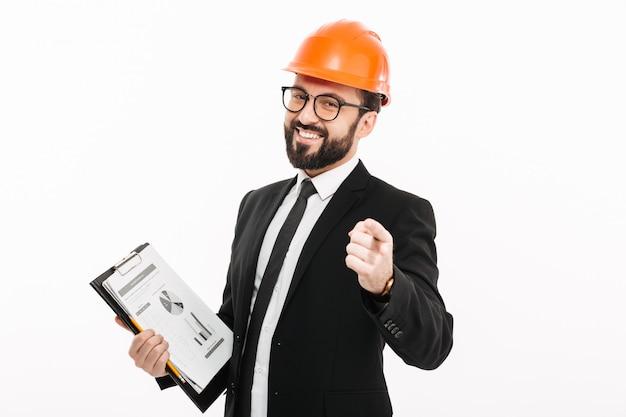 Engenheiro empresário no capacete segurando documentos apontando.