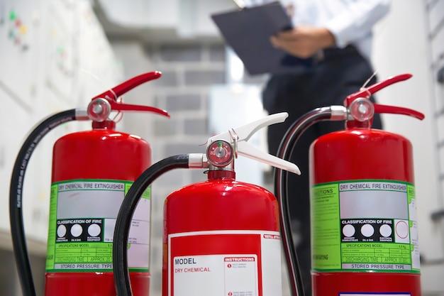 Engenheiro está verificando extintores de incêndio na sala de controle de incêndio para prevenção.