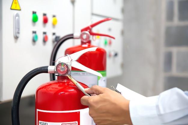 Engenheiro estão verificando e inspecionando um extintor de incêndio.
