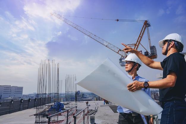 Engenheiro estrutural e trabalhador chefe com plantas discutem a inspeção da construção ao ar livre