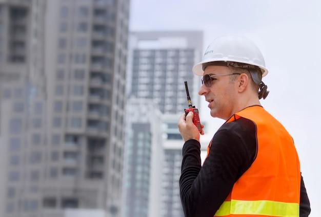 Engenheiro falando no walkie-talkie para comunicação com a equipe