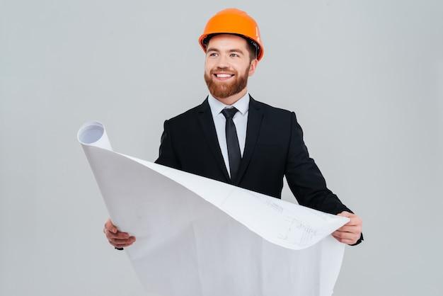 Engenheiro feliz barbudo em terno preto e capacete laranja com layout aberto, olhando de lado.