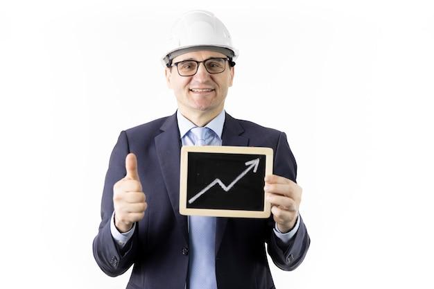 Engenheiro feliz mantém sinal com seta para cima, mostrando como o sinal de crescimento de aspas