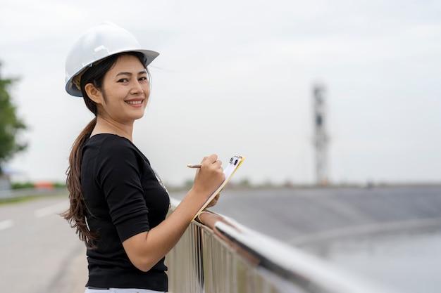 Engenheiro feminino asiático, verificando o trabalho