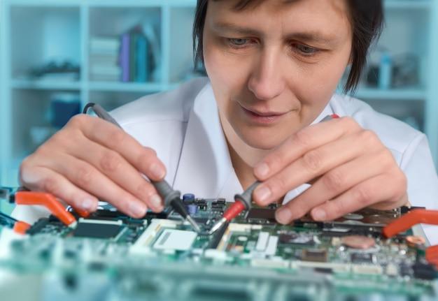 Engenheiro feminino caucasiano de meia-idade ou reparos de tecnologia com defeito