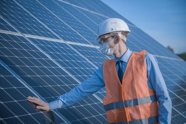 Engenheiro, homem de uniforme e máscara, óculos de capacete e jaqueta de trabalho em um dos painéis solares na estação solar