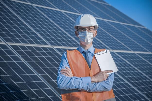 Engenheiro, homem de uniforme e máscara, óculos de capacete e jaqueta de trabalho em um fundo de painéis solares na estação solar. técnico verifica a manutenção.