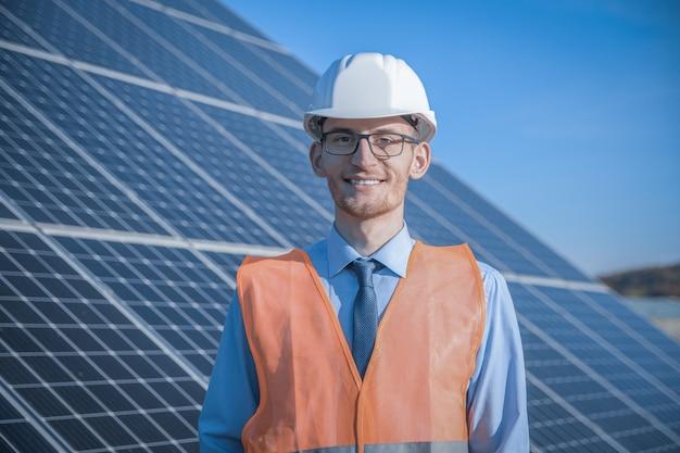 Engenheiro, homem de uniforme, óculos de capacete e jaqueta de trabalho em um fundo de painéis solares na estação solar