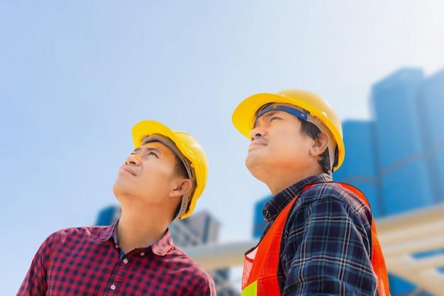 Engenheiro homem e trabalhador com traçado de recorte, verificação e planejamento de projeto no canteiro de obras, homem olhando para o céu sobre fundo desfocado