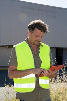 Engenheiro homem em roupas de segurança na frente do armazém industrial